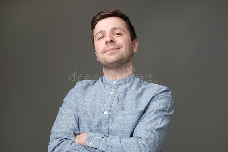 Confident young handsome man in blue shirt keeping arms crossed and smiling royalty free stock photography