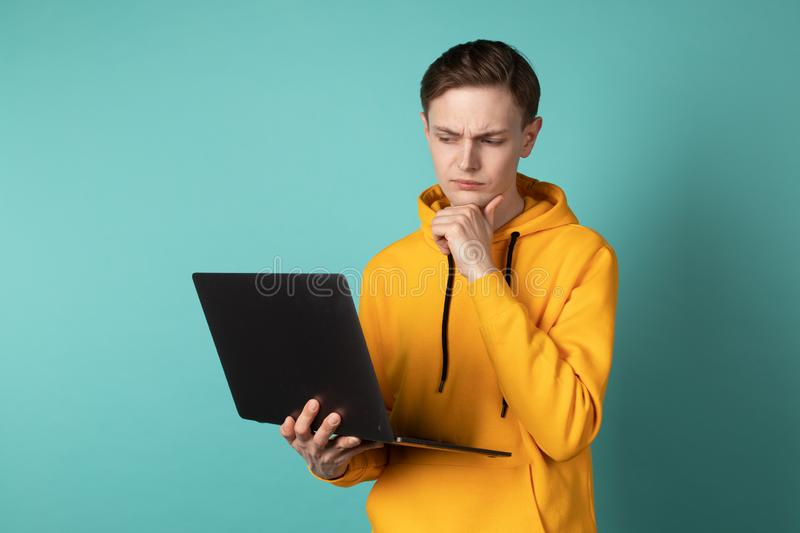 Confident young handsome man designer in yellow hoodie working on laptop while standing against blue background stock photo