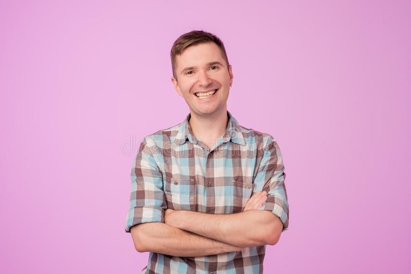 Confident young handsome man keeping arms crossed and smiling while standing against blue white background stock photos