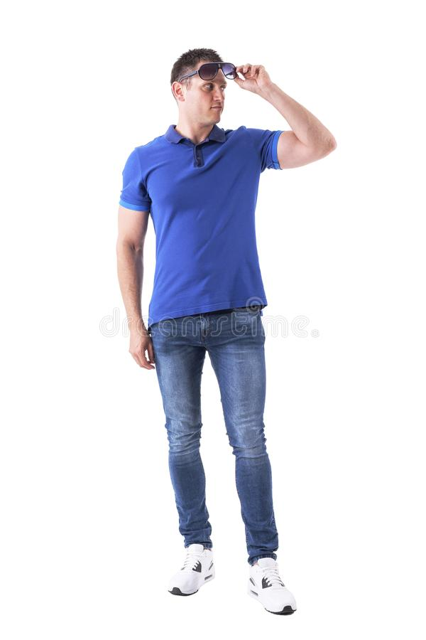 Confident young macho adult man in blue polo shirt holding and looking away under sunglasses. Full body isolated on white background stock photo