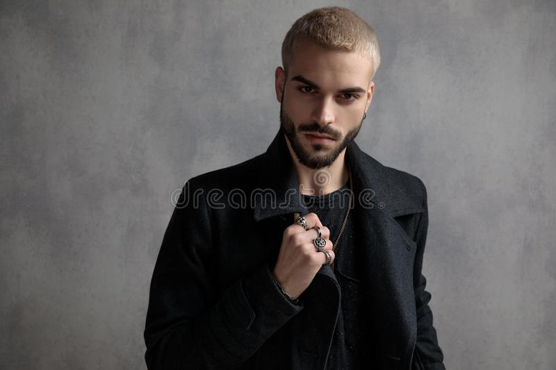 Confident young man adjusting his coat and showing his rings stock photography