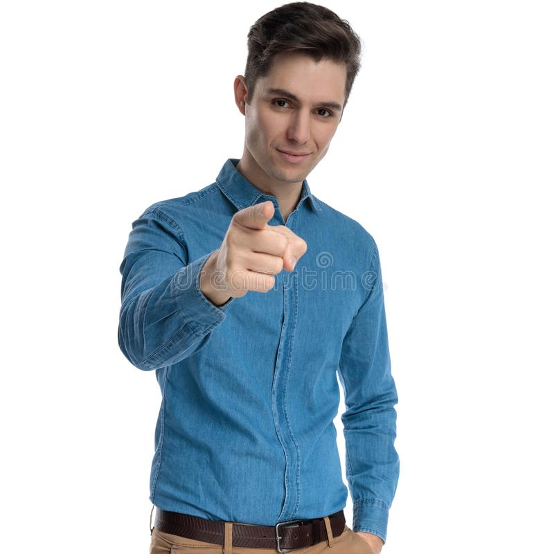 Confident young man in blue shirt smiling and pointing finger royalty free stock image