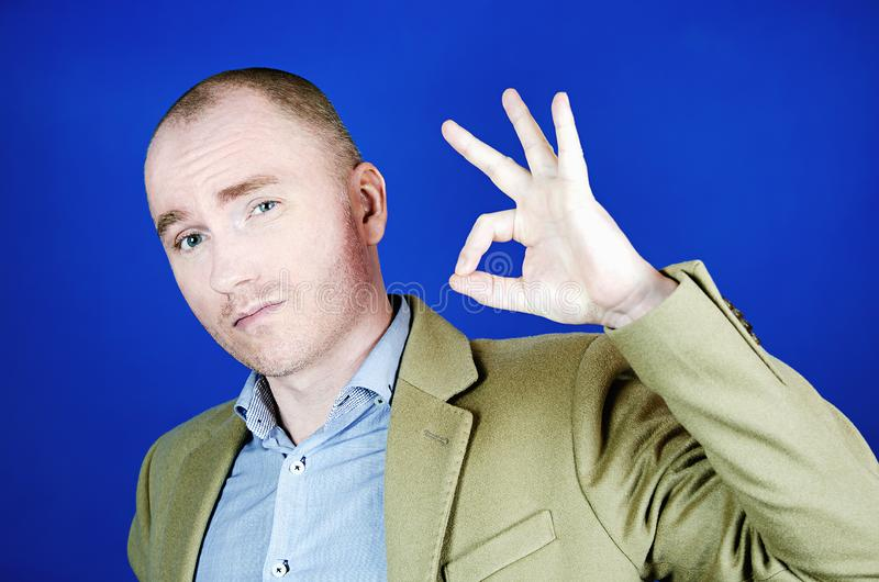 A confident young man in a cream coat shows Okey`s gesture and looks at the camera. Gesturing and signs concept. Gesturing and signs concept. A confident young stock images