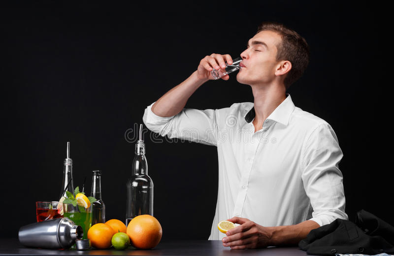 A confident young man drinking a whiskey or tequila in a club on a black background. A success businessman resting a pub stock photos