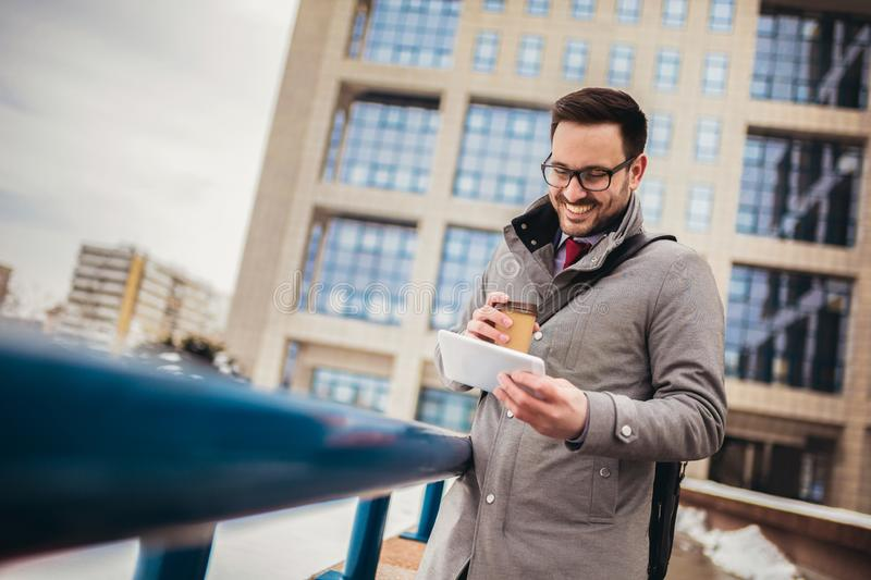 Young man in glasses drinking coffee outdoors and using digital tablet royalty free stock image