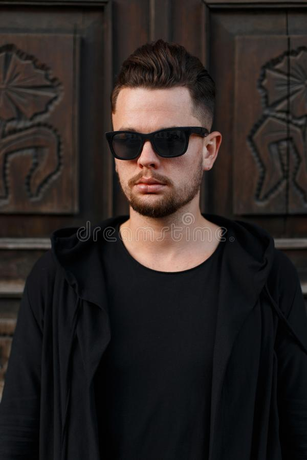 Confident young man hipster man in black stylish glasses and black fashionable clothes near vintage wooden doors. Attractive fashionable guy model stock image