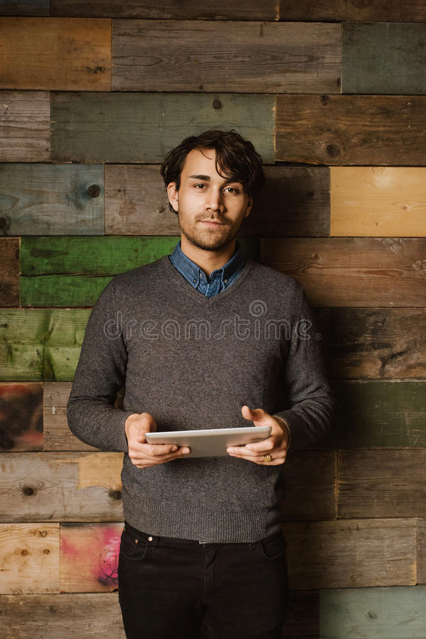 Confident young man holding a digital tablet in office royalty free stock images