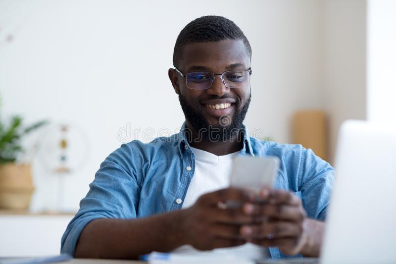 Confident young man holding smart phone and looking at it while sitting at his working place stock photography