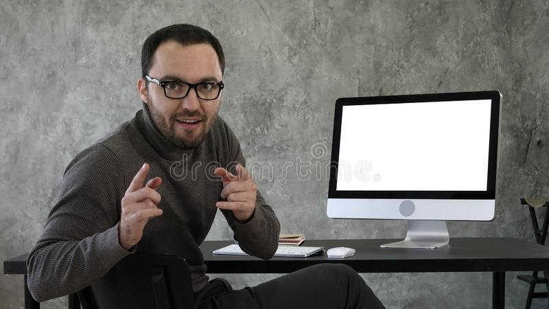 Confident young man looking at camera talking in a very confident way near computer screen. White Display. royalty free stock photography