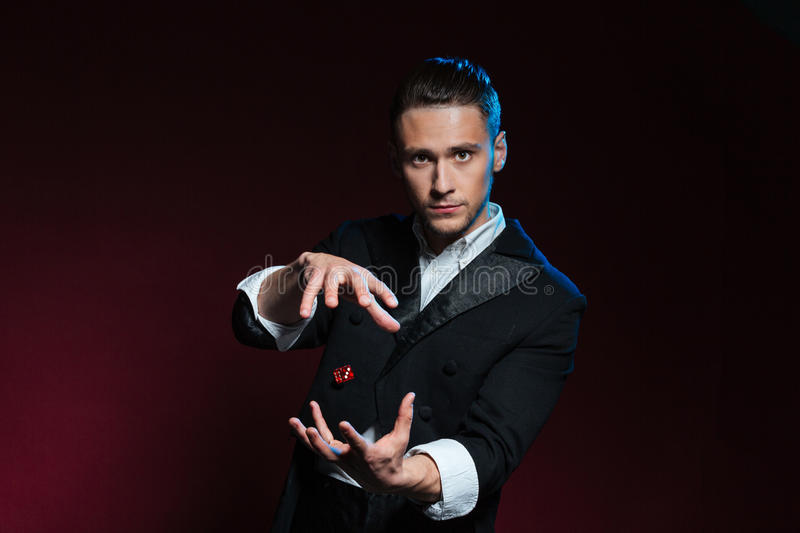 Confident young man magician showing tricks using one flying dice stock photo