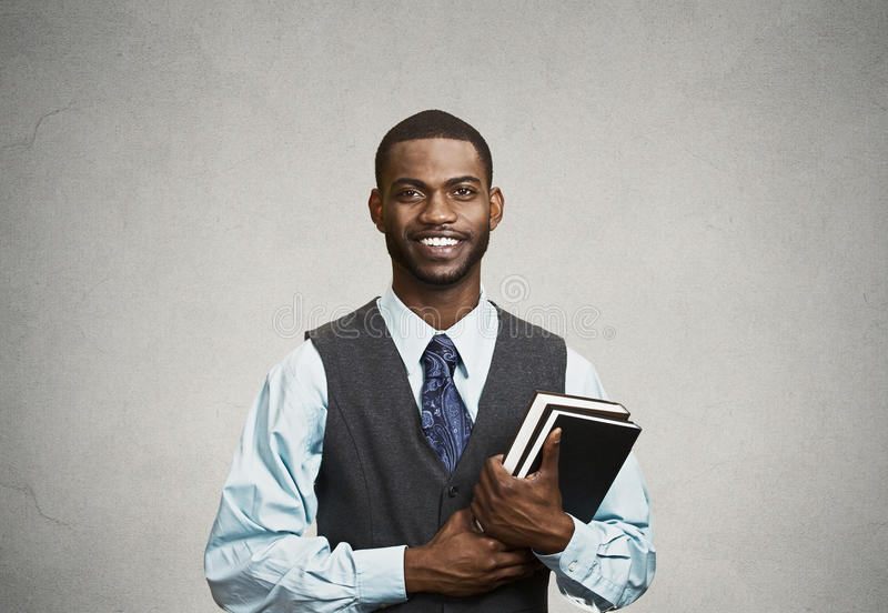 Confident young man, student holding books royalty free stock photo