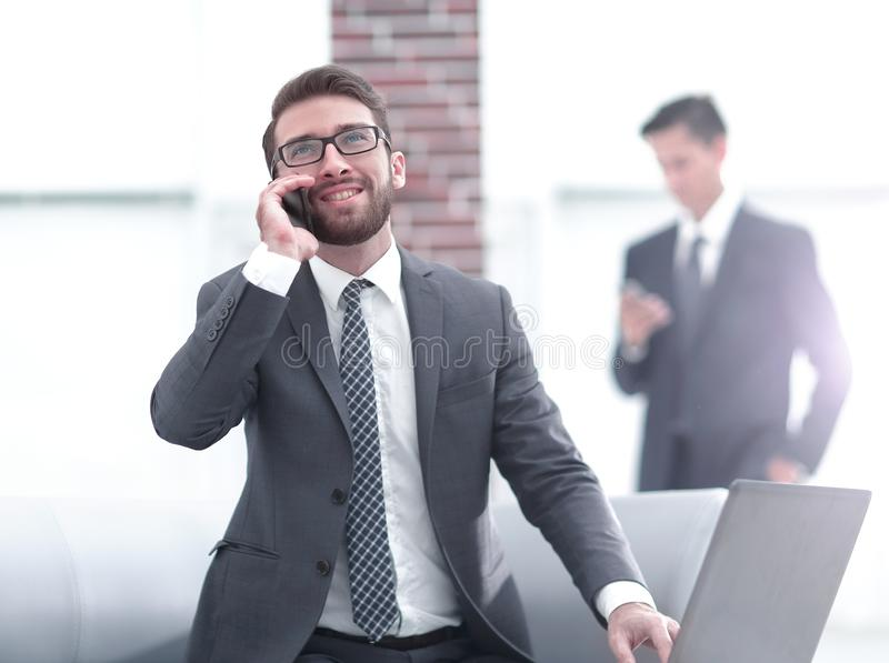 Confident young man talking on phone in office. Young smiling businessman in casual talking on mobile phone in modern white office interior stock photo