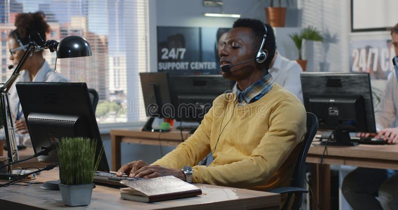 Confident young man working at a call center royalty free stock photos