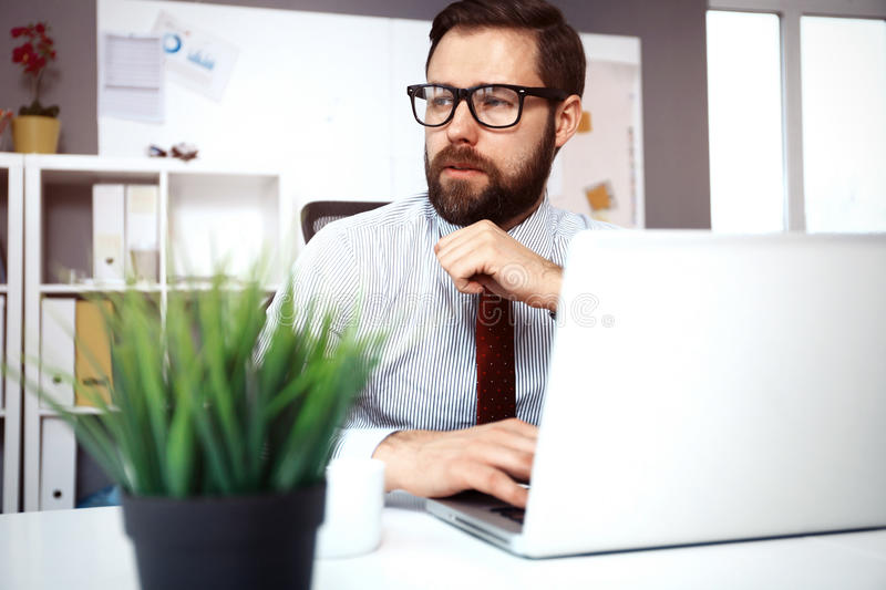 Confident young man working on laptop while sitting at his working place in office. Enjoying good working day. Confident young man working on laptop while royalty free stock photo