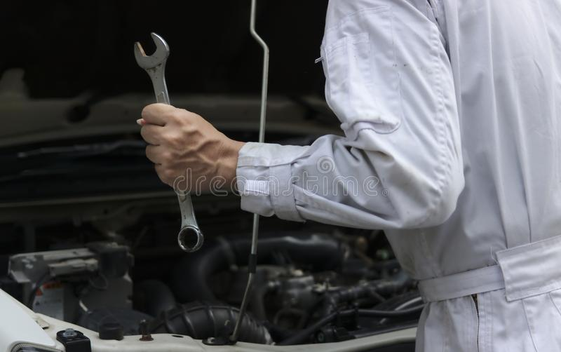 Confident young mechanic man in white uniform holding wrench with open hood at the repair garage. Car insurance concept. Confident young mechanic man in white royalty free stock photos