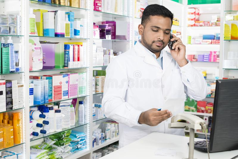 Confident Pharmacist Using Phone While Holding Prescription Pape royalty free stock photography