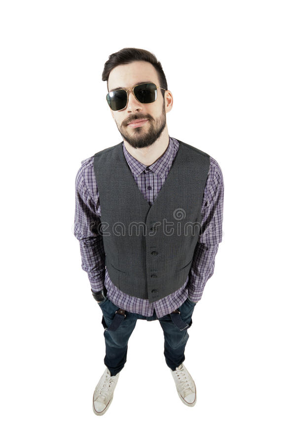 Confident young relaxed hipster with hands in pockets royalty free stock photo