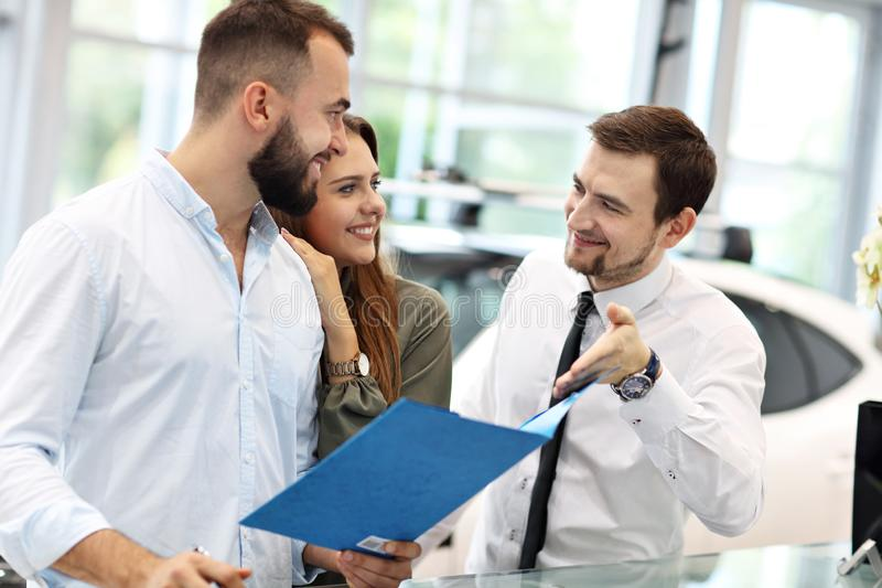 Confident young salesman explaining car features to the young attractive owners royalty free stock photography