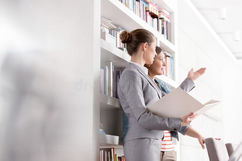 Confident young saleswoman gesturing to female client while holding document in apartment stock photo