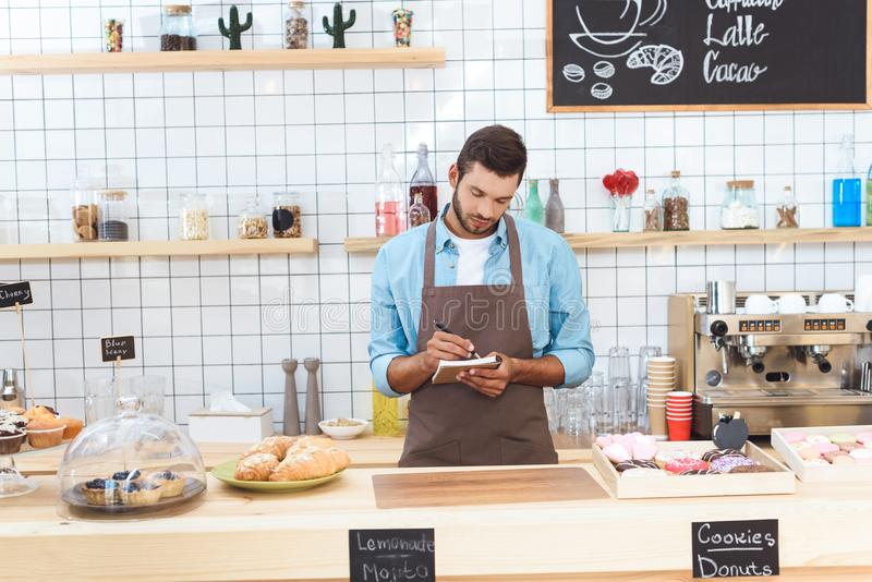 confident young small business owner taking notes while working royalty free stock photos