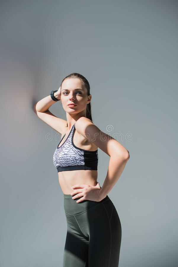 confident young sportswoman standing with hand on waist and looking away stock photo