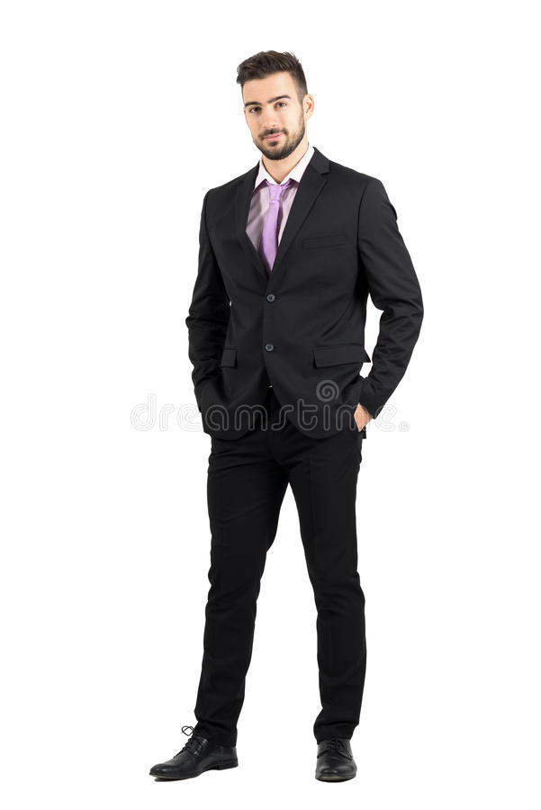 Confident young stylish man in suit looking at camera with hands in pockets stock images
