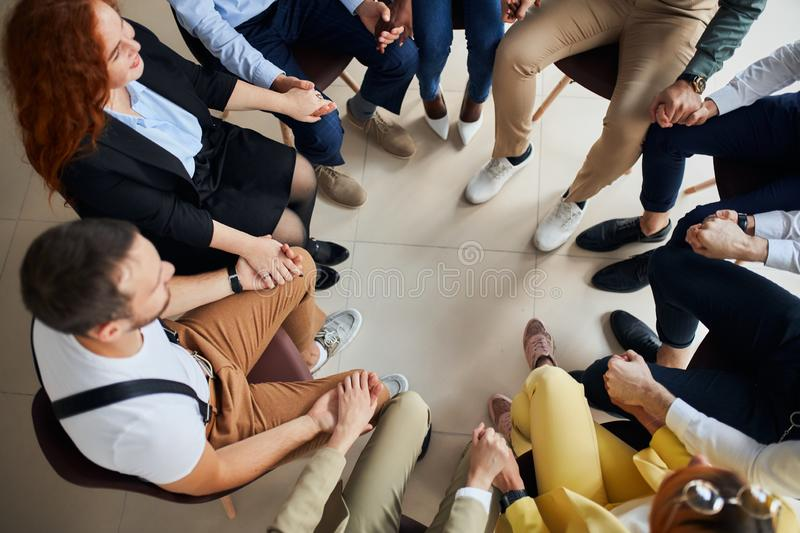 Confident young and successful leaders holding hands in circle. Young leaders, co-workers, business team hold hands together while sitting on chairs in circle royalty free stock photography