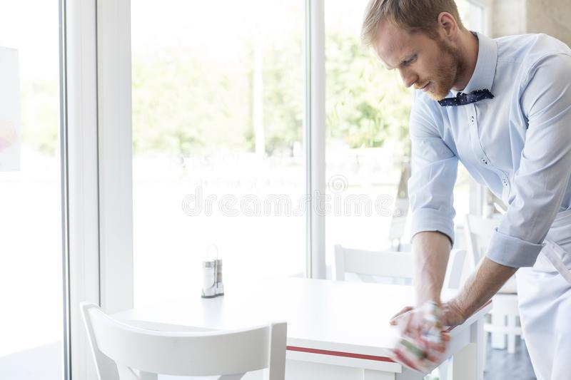 Confident young waiter cleaning table at restaurant royalty free stock photography
