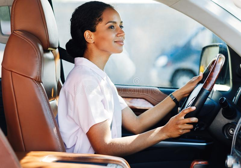 Confident young woman driving car stock photo