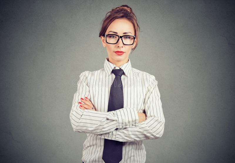 Confident woman in formal outfit and eyeglasses holding arms crossed and looking at camera royalty free stock image