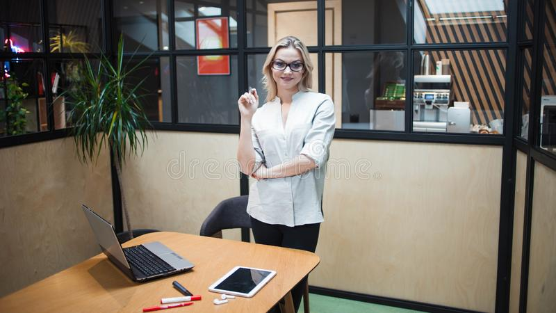 Confident young woman in her office stands near the workplace. stock images