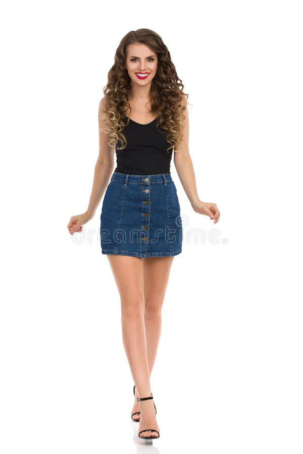 Young Woman In Jeans Mini Skirt And High Heels Is Walking Towards Camera. Confident young woman in jeans mini skirt, black top and high heels is smiling and royalty free stock photography