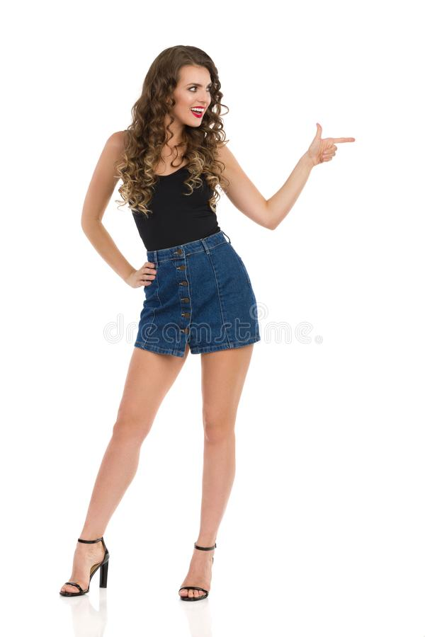 Young Woman In Jeans Mini Skirt And High Heels Is Looking Away And Pointing. Confident young woman in jeans mini skirt, black top and high heels is standing legs stock image