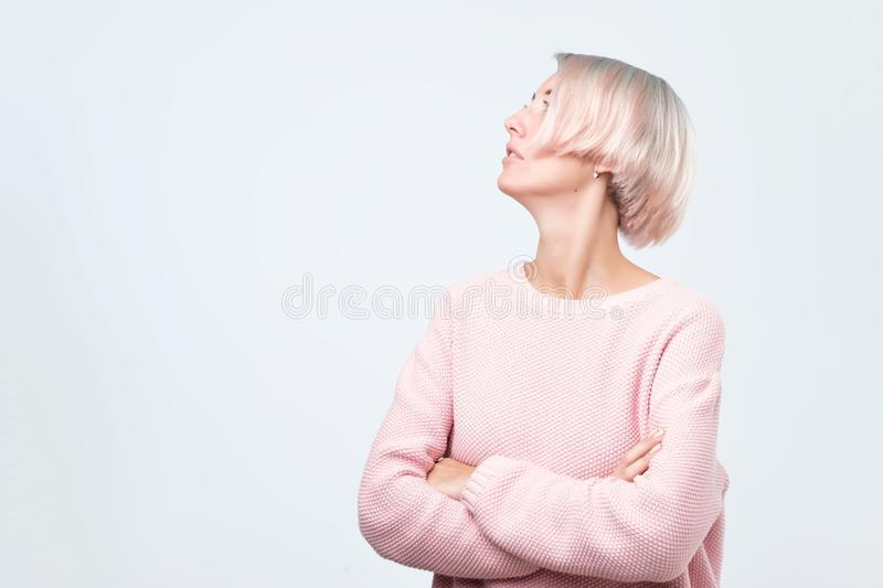 Confident young woman in pink sweater crossing her hands and looking up royalty free stock photos