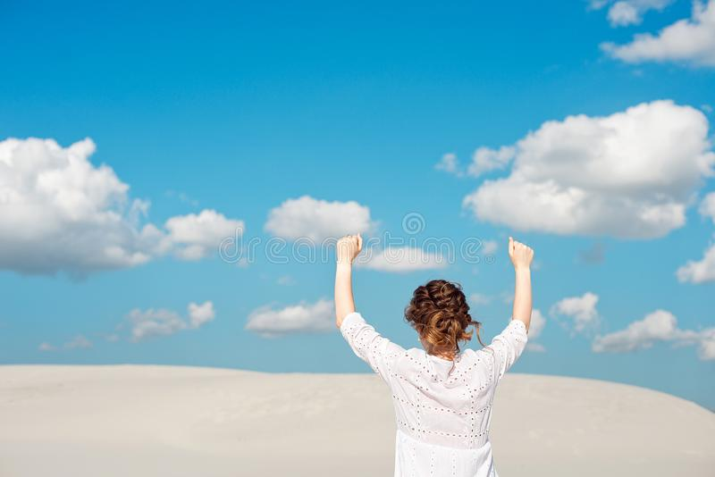 Confident young woman raising her fist up in the sky. Feeling motivated royalty free stock photos