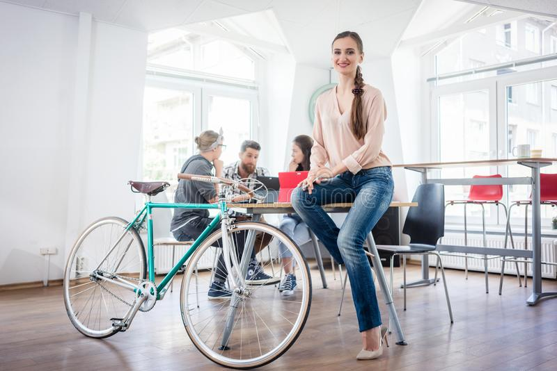 Confident young woman sitting on a desk near her commuter bike stock photo