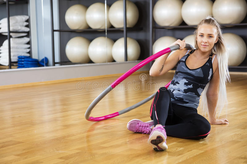 Confident Young Woman Sitting With Hoop On Floor stock image