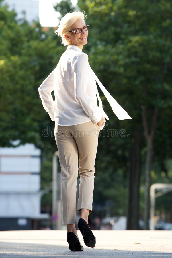 Confident young woman walking away royalty free stock photography