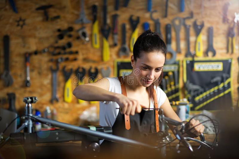 Young woman working in a bicycle repair shop royalty free stock photos