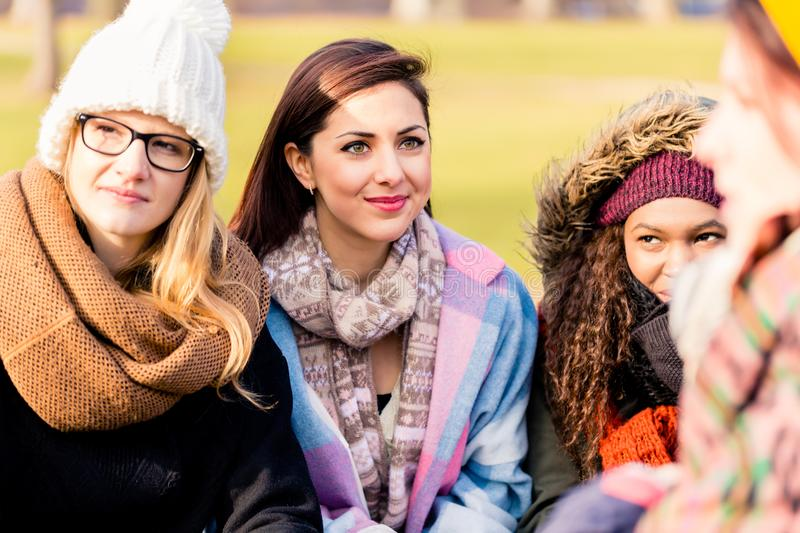 Young women daydreaming while sharing ideas outdoors royalty free stock photo