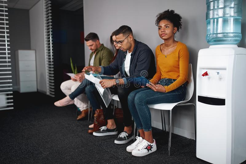 Young woman looking confident while sitting with a diverse group of job applicants in an office waiting for interviews royalty free stock photography