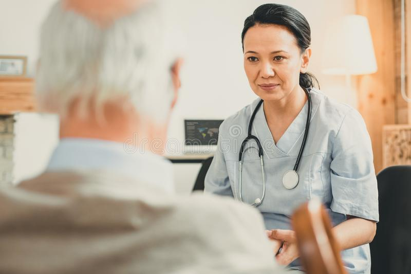 Professional nurse seriously looking on her ward. Confidently talking. Professional nurse seriously looking on her ward sitting together in consulting room royalty free stock photography