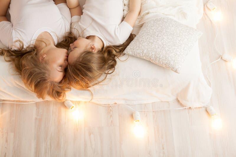 Configuração da mãe e da filha na cama e no beijo Vista de acima togetherness Interior do sotão foto de stock