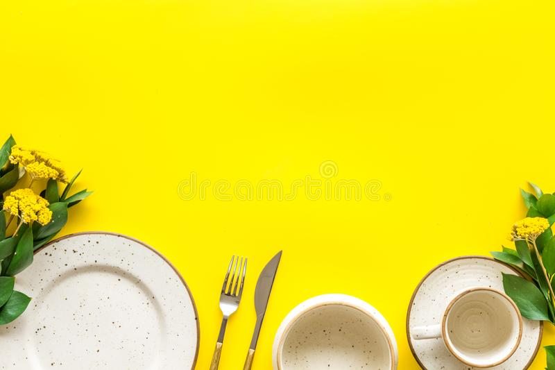 Configuração de tabela com pratos e flatware em tela de fundo amarela mock up fotografia de stock royalty free