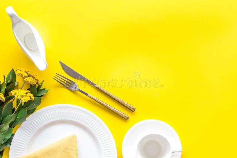 Configuração de tabela com pratos e flatware em tela de fundo amarela mock up fotos de stock royalty free