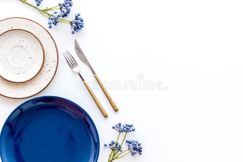 Configuração de tabela com pratos e flatware no modo de exibição superior branco imagem de stock