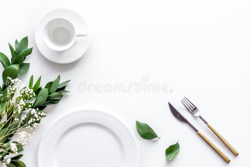 Configuração de tabela com pratos, flatware e flor em um espaço de cópia de visão superior branco de fundo imagem de stock