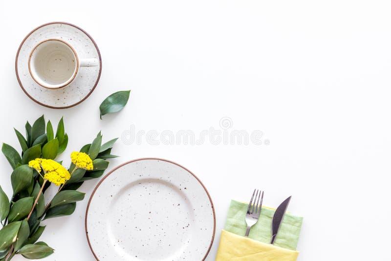 Configuração de tabela com pratos, flatware e flor em um espaço de cópia de visão superior branco de fundo fotos de stock royalty free