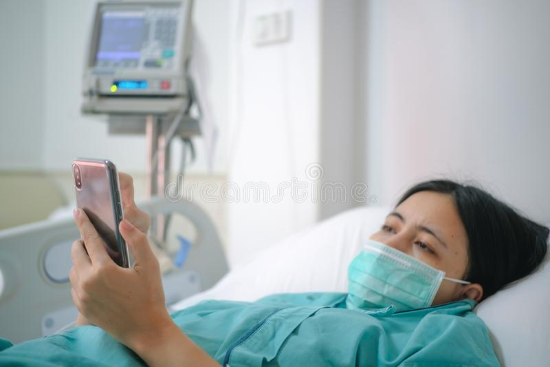 Configuração do paciente da jovem mulher na cama no hospital e no smartphone do uso imagens de stock