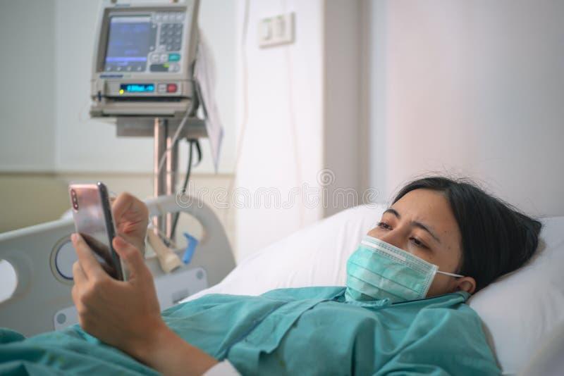 Configuração do paciente da jovem mulher na cama no hospital e no smartphone do uso imagens de stock royalty free